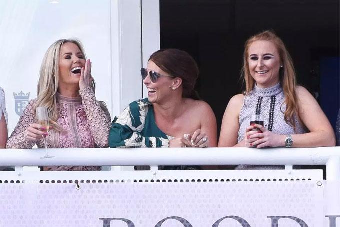 Coleen cười vui vẻ với nhóm bạn trên khán đài của trường đua.