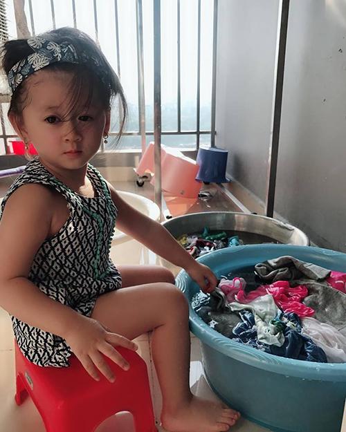 Con gái Trang Trần ra dáng thiếu nữ, ngồi bên chậu quần áo. E thương mẹ nên sáng ra mẹ ngủ quyên e lẩn thẩn lấy đồ mẹ mới mua cho e ra giặt.mẹ sanh ra e đầy thông minh và hiếu thảo.
