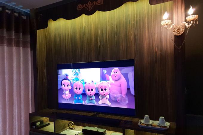 TV Qled Q7 65 inch đặt ở phòng khách với tấm panel phía sau như một sân khấu trong phim.