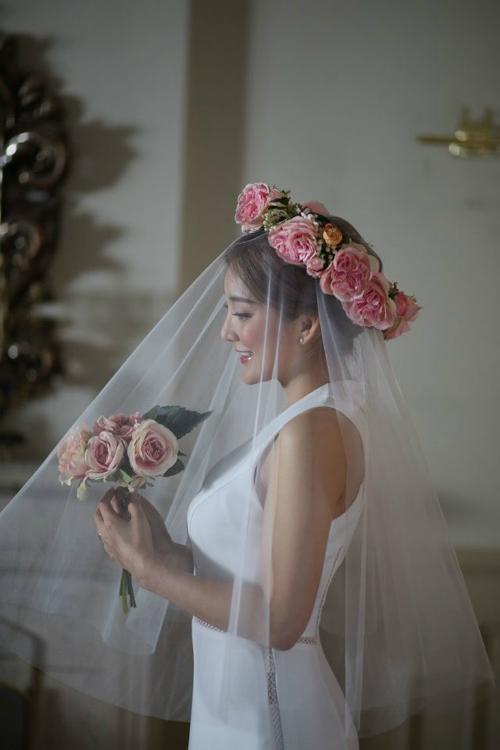 Bada của S.E.S: Chiếc váy cưới của Bada tuy không có nhiều chi tiết cầu kỳ để bình luận nhưng màu sắc nguyên bản và những đường ren nhỏ ngang eo, dọc hai bên thân là vô cùng đắt giá. Chúng tôn lên vóc dáng thanh mảnh của cô dâu. Đồng thời, cách kết hợp với vòng hoa đội đầu to bản, màu sắc rực rỡ cũng giúp cô dâu nổi bật hơn.