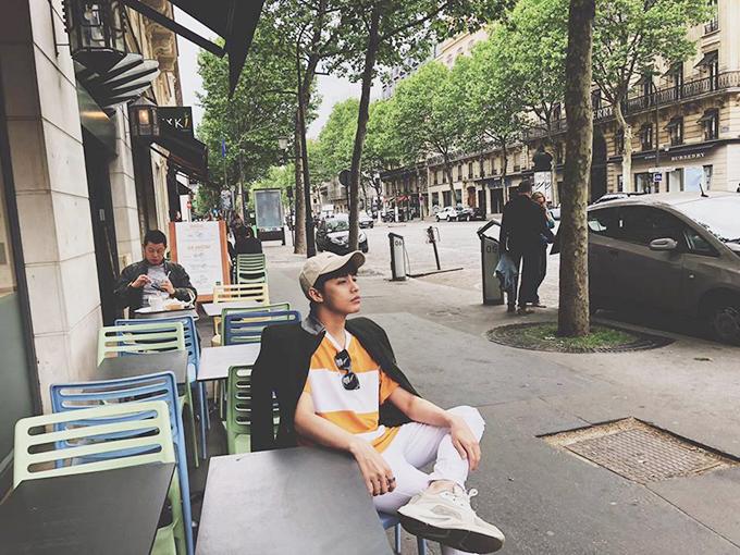 Noo Phước Thịnh thảnh thơi ngồi bên quán cà phê lề đường ở Paris.
