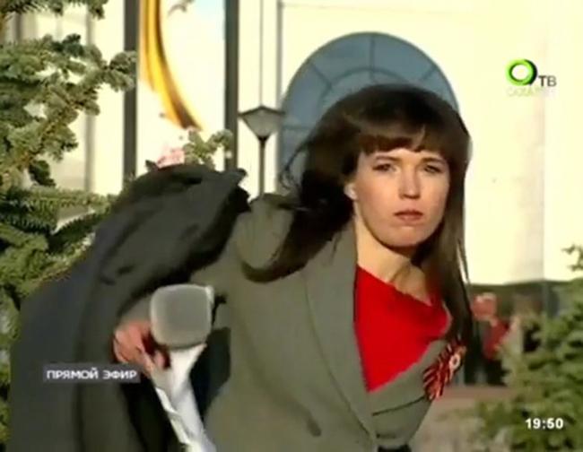 Nữ MC người Nga vội vàng cở áo để lên hình xinh đẹp. Ảnh cắt từ video.