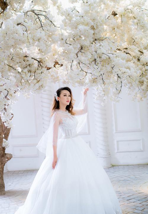 Chiếc váy cưới chiết eo, chân xòe có thể dễ dàng phù hợp với nhiều cô dâu khi nó giúp che được khuyết điểm của hình thể, tạo điểm nhấn điệu đà. Tuy nhiên, trong phim trường - nơi có không gian hẹp và nhiều bối cảnh, Kellie chọn chiếc váy chữ A có phần đuôi dài vừa phải để thuận tiện di chuyển, tạo dáng. Phần ngực cúp trái tim và tay áo xòe mỏng manh là điểm nhấn tạo cho cô dâu nét điệu đà, duyên dáng.