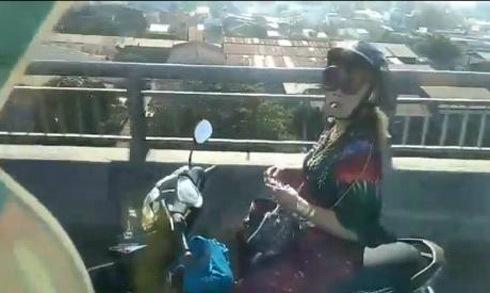 Người phụ nữ vừa đi xe máy buông hai tay vừa châm lửa hút thuốc