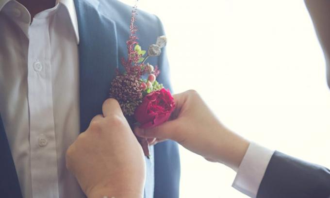 Sử dụng hoa cài áo màu đỏ lànét tinh tế cho lễ phục của chàng rể.