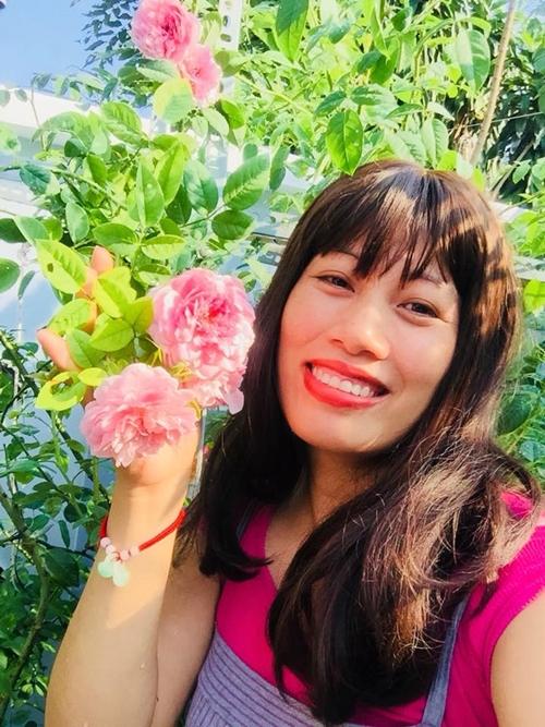 Người phụ nữ yêu hoa say sưa tạo dáng bên những đóa hồng.