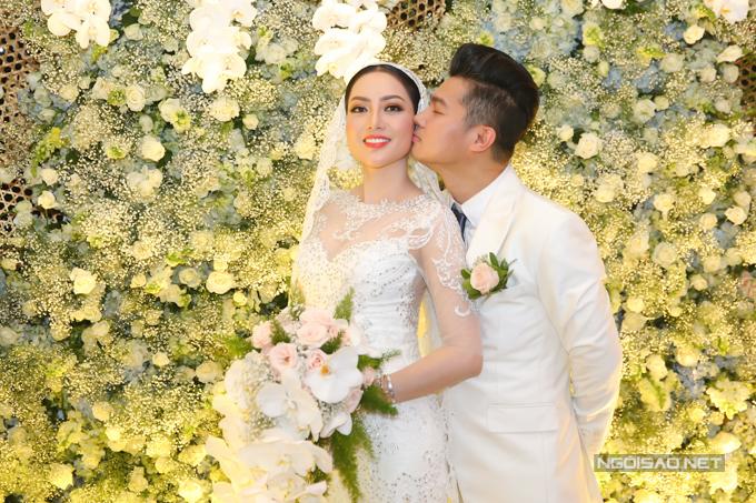Lâm Vũ âu yếm hôn má vợ yêu trong khi cả hai đang đứng đón khách.