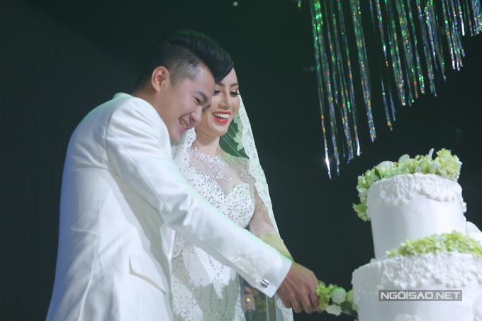 Cô dâu, chú rể hạnh phúc chung tay cắt bánh cưới.