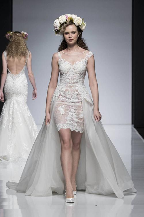 Với thương hiệu Diane Legrand, chiếc váy cưới ngắn này thật sự tinh tế. Nhờ phần tà vải tuyn dài được đính từ phần eo đằng sau, mẫu váy mang hơi hướngcổ điển của những chiếc váy cưới dáng dài. Dù vậy, thiết kế khôngđơn điệu bởi phom dáng ôm khít đường cong của người mặc và phần ren thêu tỉ mỉ.