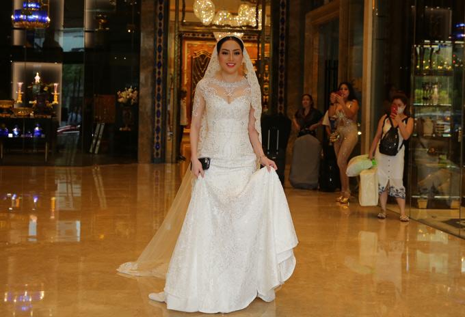 Cô dâu Huỳnh Tiên lộng lẫy trong bộ soiree trắng đứng ở sảnh khách sạn chờ ông xã. Huỳnh Tiên là Việt kiều Mỹ, từng đăng quang Hoa hậu phụ nữ người Việt thế giới 2015.