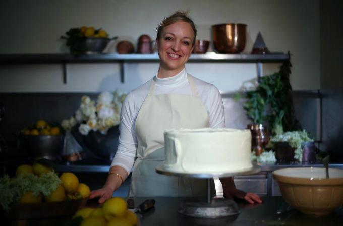 Chiếc bánh được trang trí bên ngoài với màu trắng ngà và hoa cơm cháy, phần bánh bông lan làm từ chanh hữu cơ và phần kem bơ có vị hoa cơm cháy cùng lớp xi rô hoa cơm cháy. Ảnh: The Sun.