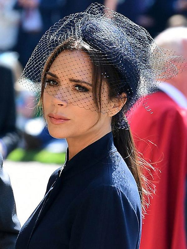 Victoria Beckham trung thành với kiểu trang điểm mắt khói đen và làn môi nude. Kiểu tóc buộc đuôi ngựa cao kết hợp với mũ và mạng che mang đến diện mạo thanh lịch, quý phái cho bà Becks.