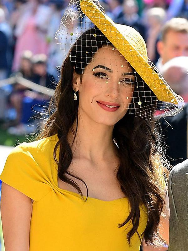 Amal Clooney diện váy và mũ vàng rất nổi bật nên cô chọn lối trang điểm tự nhiên để không khiến bản thân quá loè loẹt. Điểm nhấn trên khuôn mặt của cô là hàng chân mày đen đậm và đôi mắt khói sâu thẳm.
