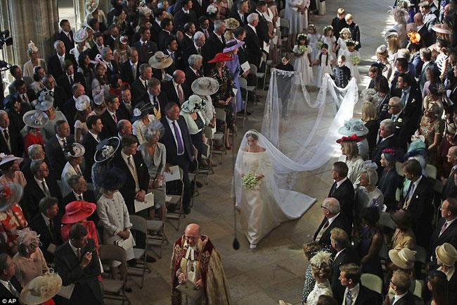 Dàn phù dâu nhí nâng váy cho cô dâu Meghan khi cô bước vào lễ đường.