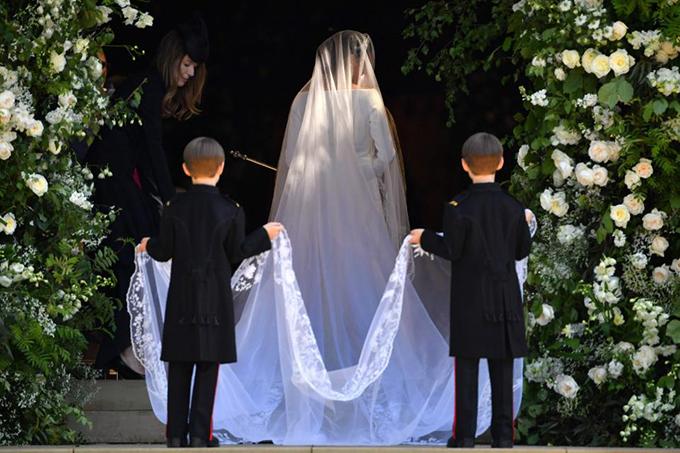 Voan trùm đầu của cô dâu dài đến 5m và được làm từ chất liệu tuyn lụa. Tóc của cô dâu được búi thấp ra phía sau.Họa tiết thêu thủ công tinh tế ở đường viền khăn voan.