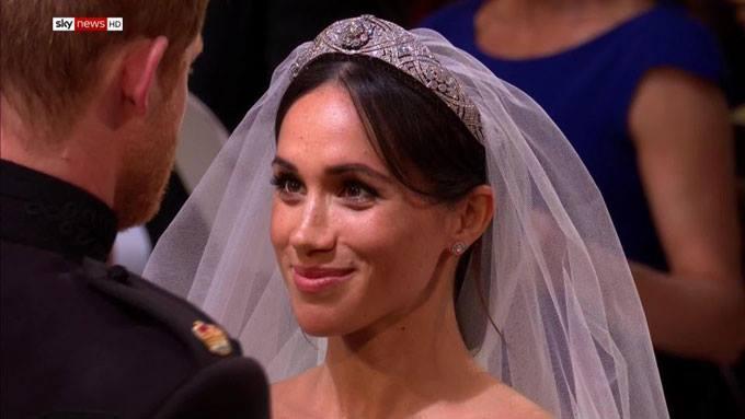 Cô dâu mỉm cười khích lệ khi chú rể nói lời thề nguyền.