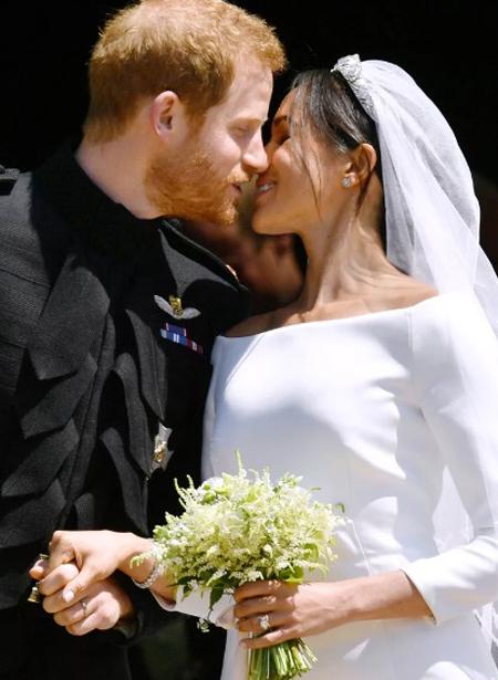 Đôi uyên ương trao cho nhau nụ hôn ngọt ngào bên ngoài lễ đường. Ảnh: Rex.