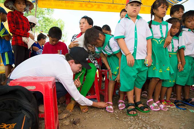 Cô tự tay mang dép mới cho các em học sinh.