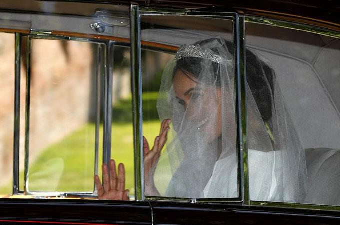 Meghan Markle vẫy tay chào dân chúng hai bên đường khi chiếc Rolls Royce chở cô rời khách sạnCliveden House ở Taplow để tới nhà nguyện St George.