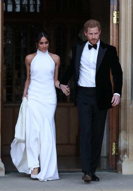 Trước đó, cô dâu chú rể thay bộ trang phục cưới thứ hai. Trong khi Meghan mặc một chiếc váy màu trắng yêu kiều được thiết kế bởi Stella McCartney, Hoàng tử Harry diện vest đen lịch lãm, thắt nơ ở cổ.