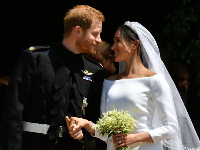 Hoàng tử Anh và vợ bước ra bên ngoài nhà nguyện St George sau hôn lễ hôm 19/5. Ảnh: AFP.