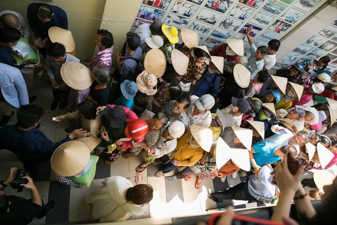 Người dân xếp hàng ngay ngắn để nhận gạo. Kèm theo mỗi bao gạo là lời động viên khích lệ tinh thần từ doanh nhân Bùi Thị Hà.
