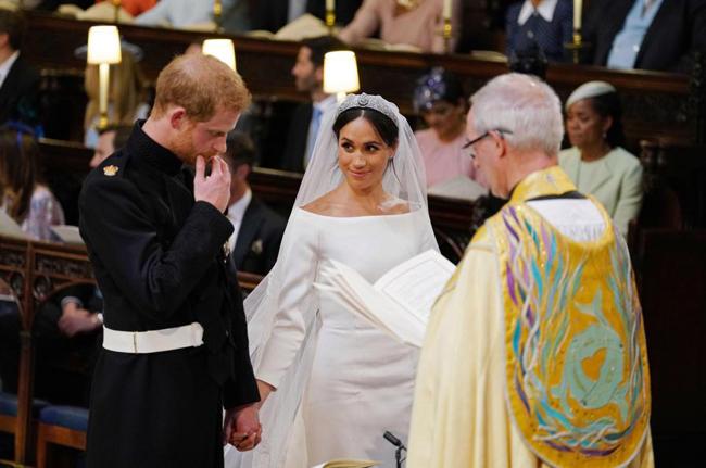 Meghan quay sang nhìn và trấn an chồng khi đứng trước bàn thờ. Ảnh: AFP.