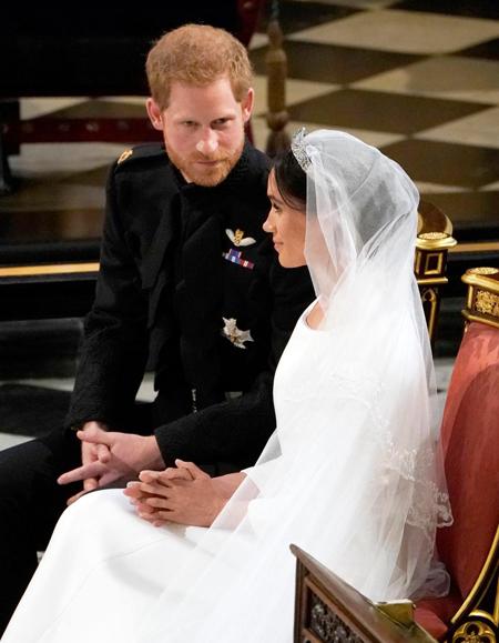 Meghan nhìn thẳng trong khi Harry bối rối. Ảnh: AP.
