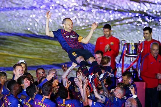 Iniesta được các đồng đội tung lên cao trong lễ đăng quang.