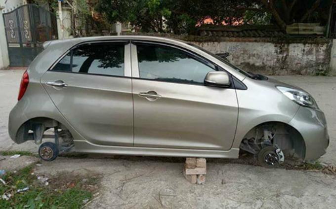 Chiếc xe bị tháo rời hai bánh và kê gạch ở gầm. Ảnh: Hùng Nguyễn