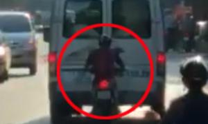 Thanh niên chạy xe máy sát đuôi ôtô để tránh nắng