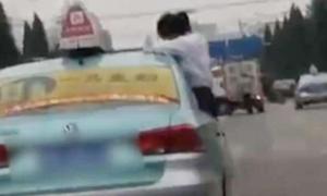 Nữ sinh làm bài tập trên nóc taxi đang chạy