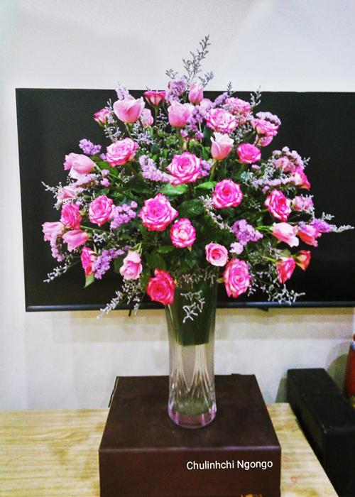 Chị Ngô Thúy gợi ý cách cắm bình hoa trang trí phòng khách từ hoa hồng, salem và sao tím với giá chưa tới 50.000 đồng.Chuẩn bị:- 40 bông hoa hồng (giá 20.000 đồng mua tại chợ đầu mối)- 1 bó salem + sao tím (giá 15.000 đồng)- 1 miếng mút xốp (giá 10.000 đồng)Hoa mua về nên cắt bớt cuống, ngâm trong xô nước trước khi cắm để tươi lâu hơn.