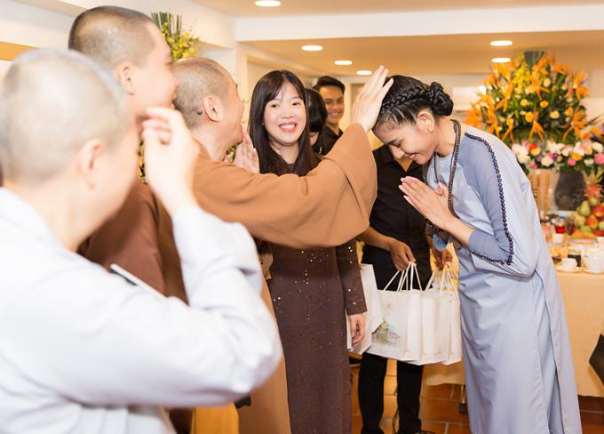 Người đẹp gặp gỡ nhiều vị tăng ni, Phật tử trong buổi khai trương cửa hàng bán trang phục đi lễ chùa. Cô được một vị sư chạm tay lên đầu, ban phúc lành.