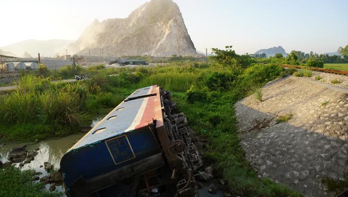 Một toa tàu nằm dưới vệ đường, cách đường ray vài mét.