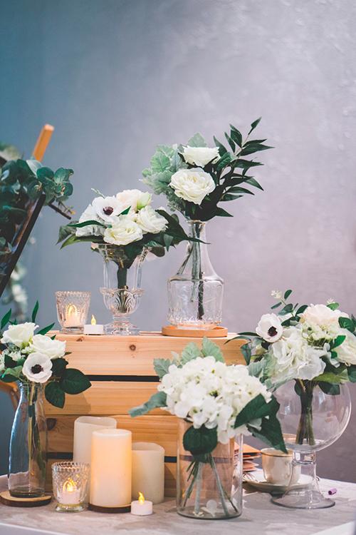 Quầy tiếp tân của tiệc cưới được trang trí ngập tràn sắc trắng. Trên bàn là nến thơm, các khối hộp gỗ, bình hoa trong suốt cắm hoacẩm tú cầu, mẫu đơn và hoa hồng trắng. Không gian được tô điểm bởi sắc trắng trung tính và màu nâu vàng.