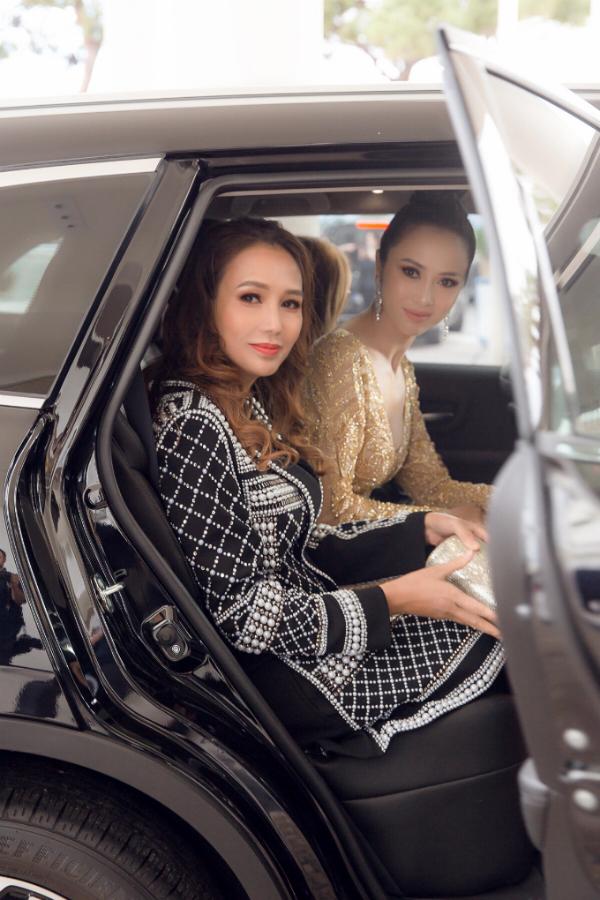 Diễn viên Vũ Ngọc Anh (váy vàng) và doanh nhân Quyên Trần - CEO của hệ thống Trung tâm thẩm mỹ Clair ngồi trên xe sang màu đen tới sự kiện.