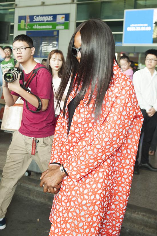 Khi xuất hiện tại sân bay, siêu mẫu liên tục cúi mặt, né tránh ống kính của các phóng viên ảnh. Siêu mẫu báo đen đến Việt Nam theo một lời mời của công ty Mỹ, mọi thông tin về hợp đồng công việc đều được giữ kín.