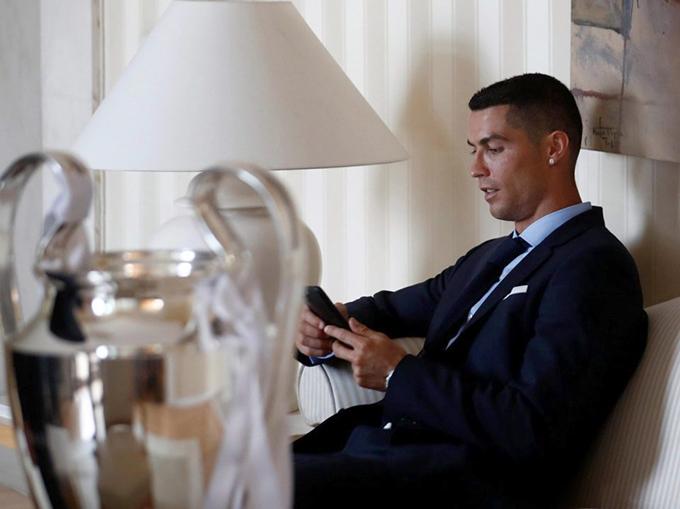 C. Ronaldo ngồi xem điện thoại, thư giãn trước giờ lên xe diễu hành.