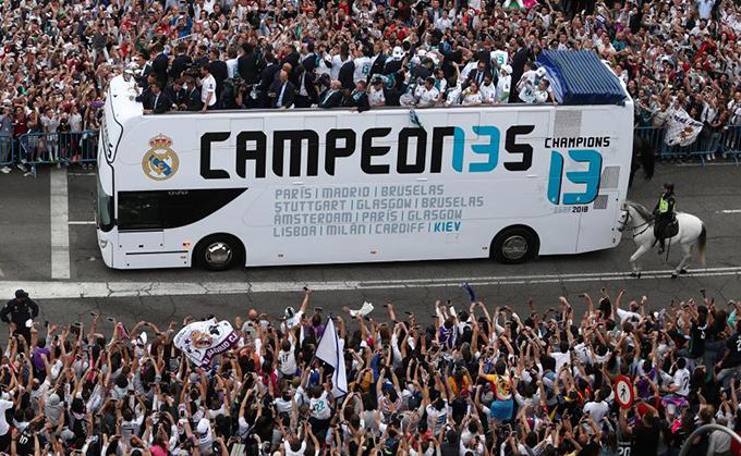 Các fan đứng chật cứng hai bên đường vẫy chào thầy trò Zidane. Đây là chiếc Cup Champions League thứ ba liên tiếp của Real và thứ 13 trong lịch sử CLB.