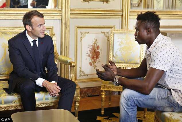 Tổng thống Pháp Emmanuel Macron trò chuyện và tuyên dương người thanh niên dũng cảm cứu người. Ảnh: AP.