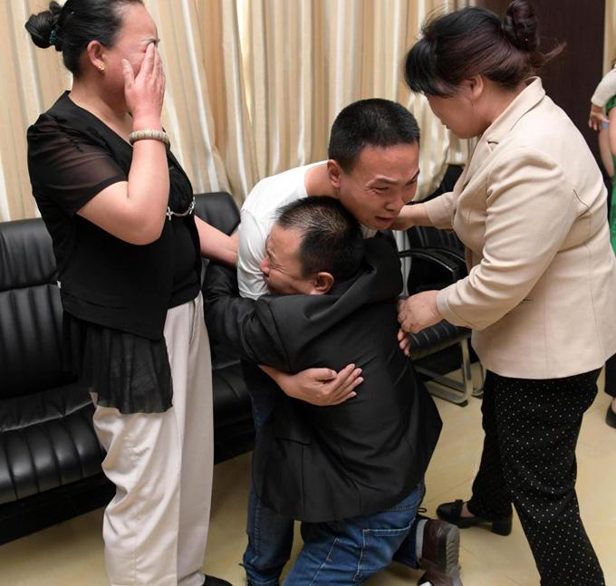 Ông Li Shunji xúc động quỳ xuống ôm chặt cậu con trai 24 năm không được nhìn thấy mặt. Ảnh: AsiaWire.