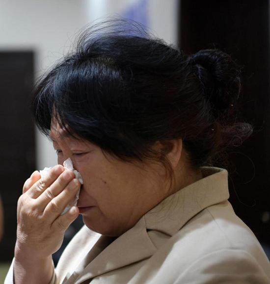 Bà Du Li không ngừng lau nước mắt vì vui sướng khi gặp lại con trai. Ảnh: AsiaWire.