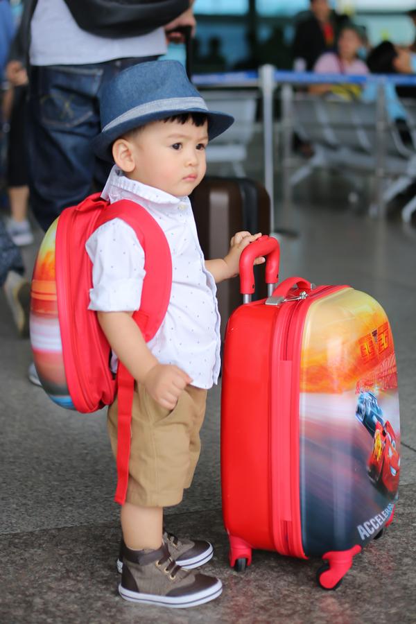 Bé được ba mẹ chuẩn bị riêng hai hành lý để xuất ngoại.