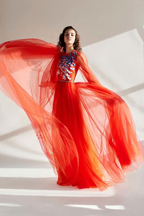 1. Mẫu váy đỏ bằng vải tuyn: Váy với chất liệu vải tuyn đem đến nét nhẹ nhàng, thanh thoát cho nàng dâu. Sự xuất hiện chấm phá của sắc xanh trên nền đỏ không hề đối chọi thị giác gay gắt bởi có thêm sự pha trộn từ màu trắng trung tính trên thân váy. Mẫu thiết kế này nằm trong bộ sưu tập mùa thu 2018 của thương hiệu Carolina Herrera.
