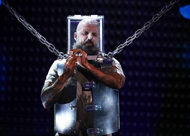 Matt Johnson trói mình bằng khóa và xích sắt trước khi chui đầu vào bể kính ngập nước.