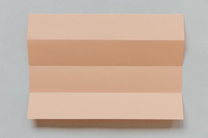 Bước 9. Gấp giấy màu cam thành bốn phần bằng nhau theo chiều dọc và cắt thành dải.