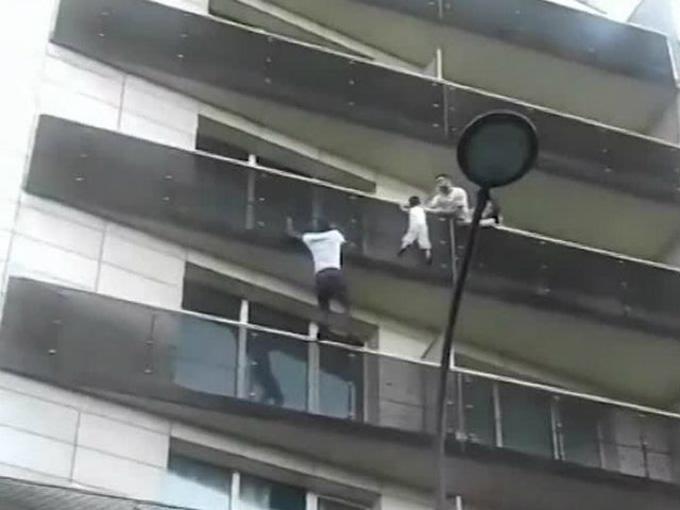 Gassama khiến nhiều người khâm phục khi tay không trèo 4 tầng nhà cứu bé trai lơ lưng ở ban công. Ảnh chụp từ video.