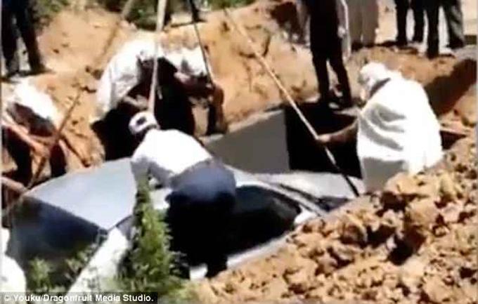 Chiếc xe được máy xúc đặt xuống huyệt trước khi lấp đất. Ảnh: Youku.
