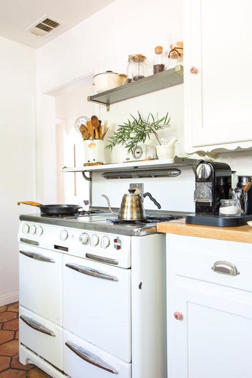 Phòng bếp là nơi khiến Megan cảm thấy bối rối khi phải tạo cho nó một diện mạo thật bảnh. Một mặt, cô thích gạch lát sàn và bếp kiểu cổ điển, nhưng phần còn lại của căn bếp lại rất chướng mắt. Người chủ trước đã sơn tường màu đỏ và Megan đã cố gắng cân bằng bằng cách sơn những chiếc tủ màu trắng.